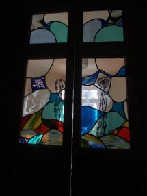 Recent window, free flowing designs with sandblasted blue on white flower on left and painted rose from my college days (40 years ago) on the right. Some sandblasted clear too.